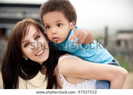 A white mother with a son of an african descend relaxing together outdoor. - stock photo