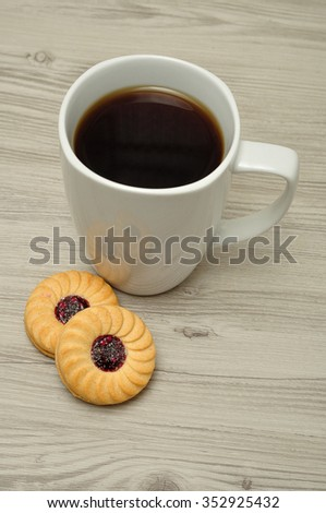 A white mug with coffee and round jam filled biscuits