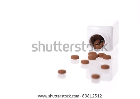 A white pill bottle with red generic pills  on a white background. - stock photo