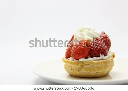 A white plate with a dessert with strawberries and cream on top. - stock photo