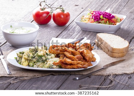 A white plate with fresh, crispy fried chicken and potato salad on wooden table - stock photo