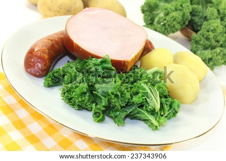 a white plate with kale, smoked meat and pee sausage - stock photo