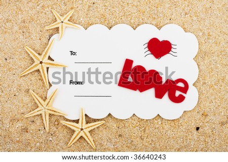 A white postcard with a red heart and the word love on a sand background, love postcard - stock photo