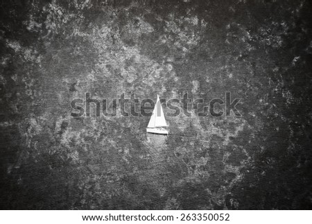 A white sailing boat  navigated by sailor in the sea. Retro aged photo with scratches and grungy texture. Black and white. - stock photo