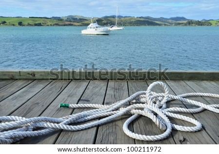 A white sailing rope on a wharf pier with boats in the background. - stock photo
