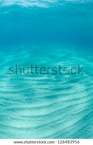 A white sand bottom in clear Caribbean water has ridges formed parallel to shore by wave and currents. - stock photo