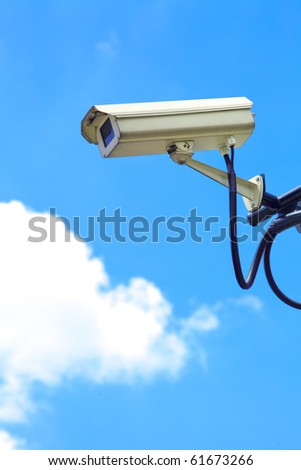 A white security camera and blue sky - stock photo