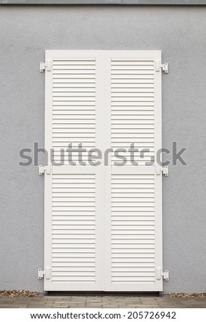A white shutter on a dark grey wall - stock photo