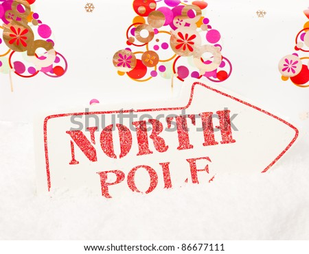 A white sign showing the way to the north pole sat in snow - stock photo