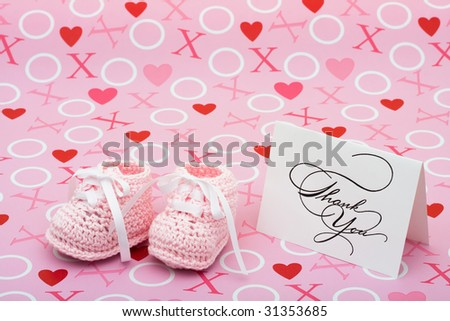 A white thank you card with baby booties on a pink love background, thank you note - stock photo