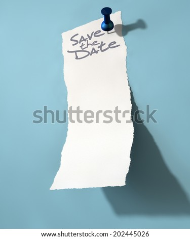 A white torn note that says save the date peeling upwards attached to an isolated blue wall background by a blue push pin - stock photo
