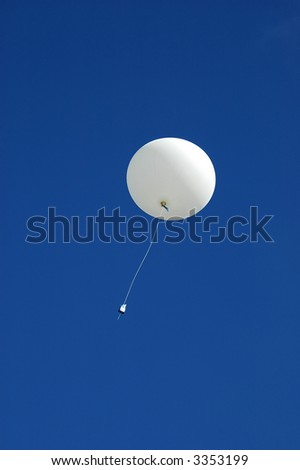 A white weather balloon is ascending into the blue sky. Picture was taken during a 3-month Antarctic research expedition.