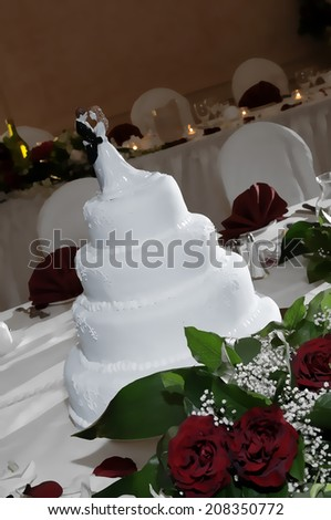 A white wedding cake with figurines of the bride and groom illustration - stock photo