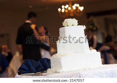 a white wedding cake with neat little swirl details and silver candy buttons, bride and groom are dancing in the background - stock photo