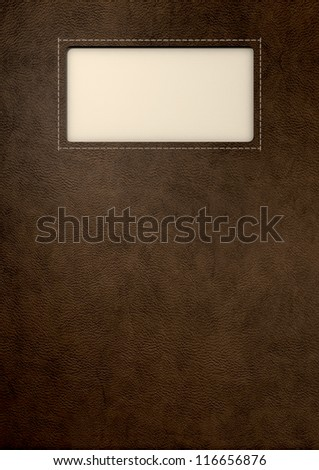 A white woven clothing label sewn into a window cut out of brown leather - stock photo
