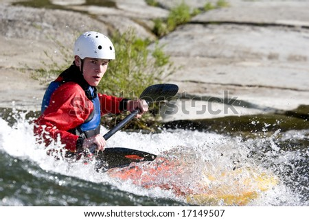 a whitewater kayaker surfing on a wave - stock photo