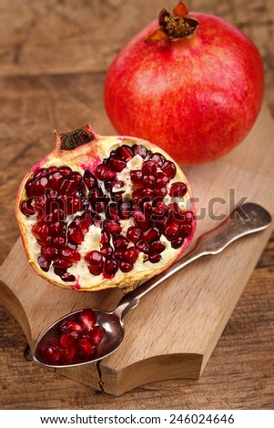 A whole and a half-cutted pomegranate with silver teaspoon and seeds - stock photo