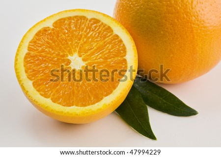 A Whole and a Half Orange Isolated on White with Leaves Horizontal - stock photo