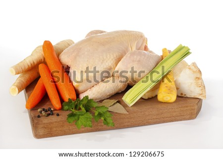 A whole chicken and soup vegetables for a chicken stock