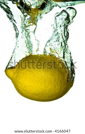 A whole lemon plunged into water on a white background - stock photo