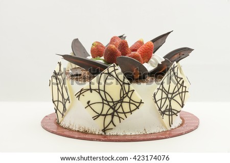 A whole round cake with topping of fresh strawberry fruits on white cream, sprinkle with cocoa powder and decorated with chocolate shards and sheets - stock photo
