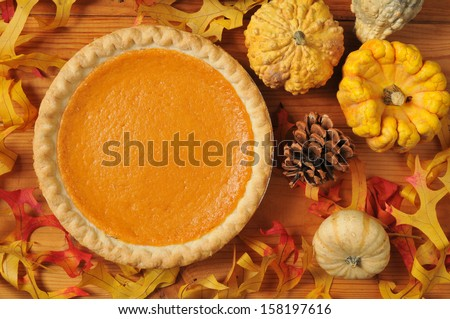 A whole sweet potato pie on an artistic set with autumn leaves, squash and gourds. - stock photo