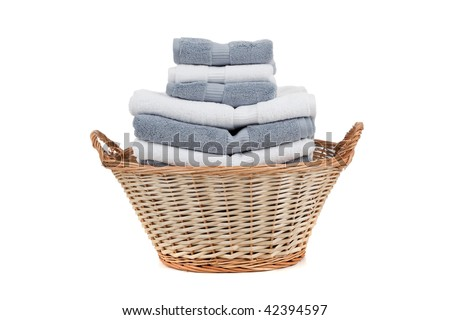 A wicker laundry basket full of white and gray towels on a white background - stock photo