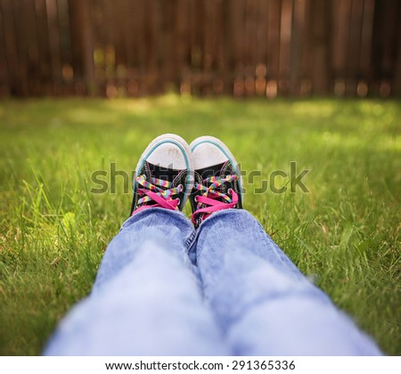 a wide angle photo of a pair of generic looking shoes like converse sneakers with pink shoe laces (SHALLOW DOF on the left shoe laces) - stock photo