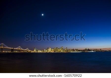 A wide angle shot of the San Francisco skyline and Bay Bridge at twilight. - stock photo