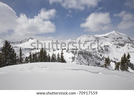 A wide angle  shot with peaks behind a snow bowl. - stock photo