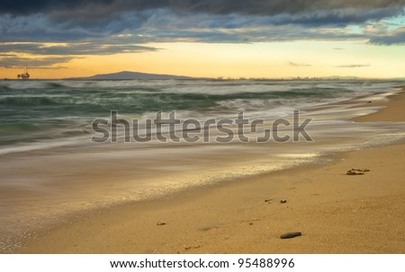 A wide shot looking out from Huntington Beach north to Long Beach and the Pal os Verde Peninsula during a windy stormy February day. - stock photo