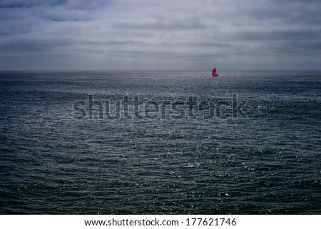 A wide shot looking out to the Pacific Ocean at a sail boat with a big red spinnaker sail. - stock photo