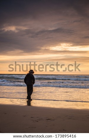 A wide shot of a young boy looking out to a sunset in Huntington Beach. - stock photo