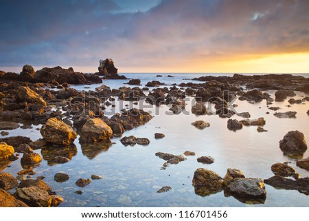 A wide shot of Corona Beach in Newport Beach California during sunset. - stock photo