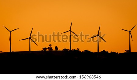 A wind-farm at sunset in rural Australia - stock photo