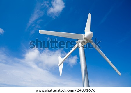 A wind turbine against a cloud blue sky - stock photo