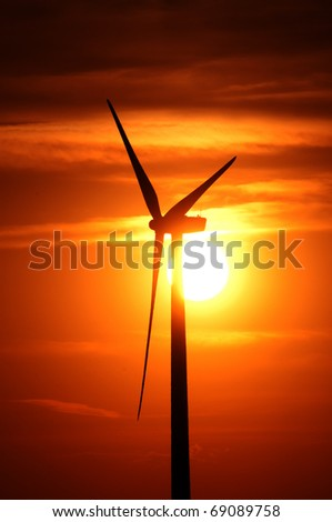 A wind turbine is silhouetted by the setting sun - stock photo