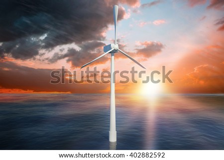 A wind turbine is working against orange and blue sky with clouds
