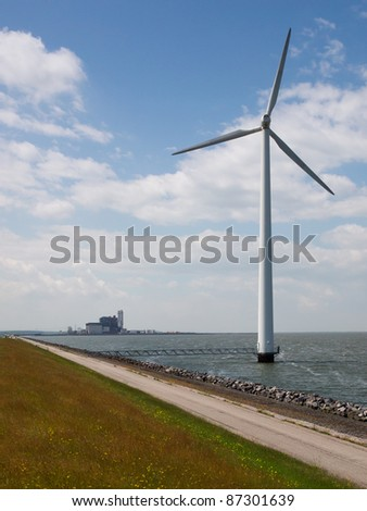 A wind turbine with a fossil fueled power plant in the backdrop