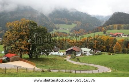A winding country road curves between green fields and autumn trees leading to a farmhouse on a beautiful hillside ~ Scenery of romantic fall countryside in Ramsau, Bavaria Germany ( Close-up version) - stock photo