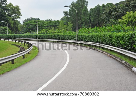 A Winding Road Going Up-Slope With Road Barriers - stock photo
