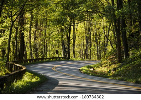 a winding road in the mountains early in the morning - stock photo