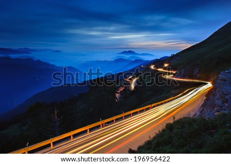 A winding road on a mountain being lit up at night. - stock photo
