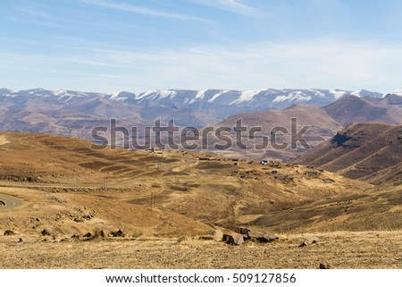 A winding road passes though the dry winter landscape of rural Leribe in the mountain kingdom of Lesotho