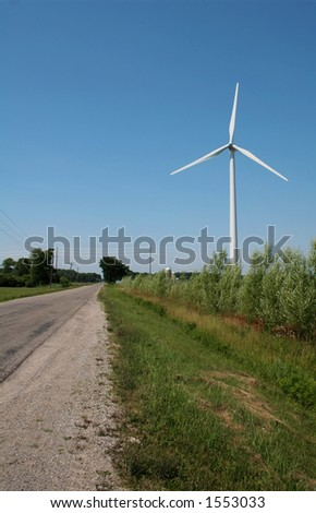 A windmill power generator on the side of the road in the middle of farm land.