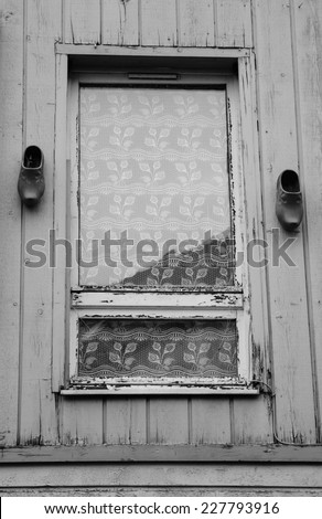 A window decorated with lace curtain (leaf pattern) and traditional dutch wooden shoes hanging at weathered plank wall. (Amiens, Picardy, France)  Rustic background. Aged photo. Black and white. - stock photo