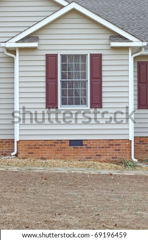 A window in a vinyl sided house with a curtain in it on a brick foundation along with gutters on both sides with room for your text. - stock photo