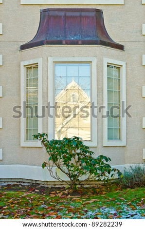a window in shadow reflecting modern house building at winter with patches of snow at lawn