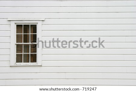 A window on the side of an old house. - stock photo