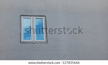 a window that reflect blue sky on the cement wall - stock photo